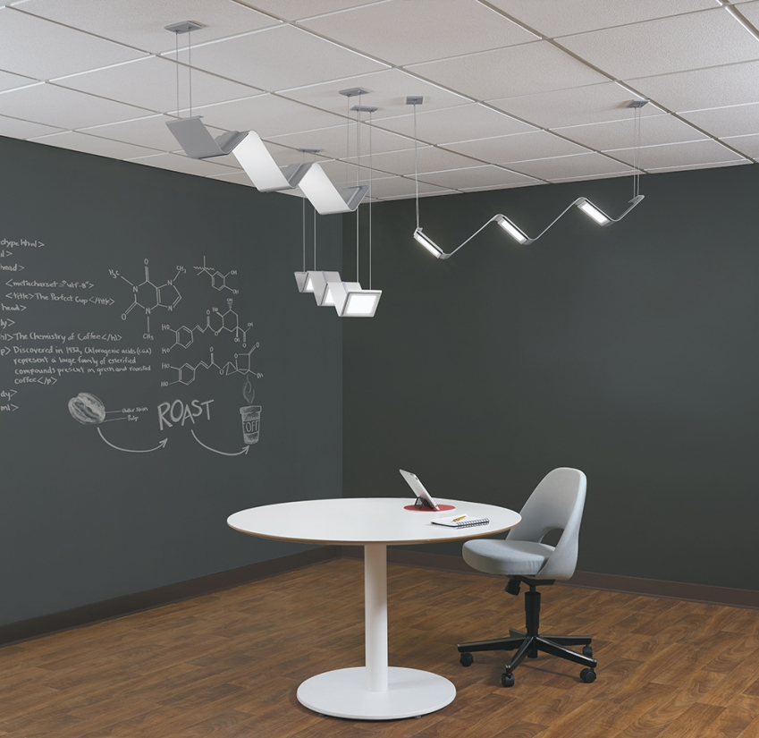 Limit office lighting fixtures above a small work table in a modern workplace setting.