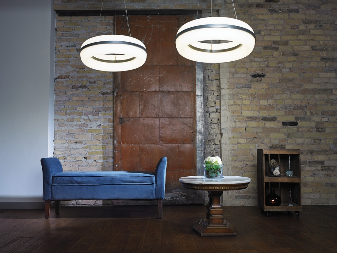Meridian Round pendant is perfect for hospitality lighting, seen here above a blue sofa in a modern loft.
