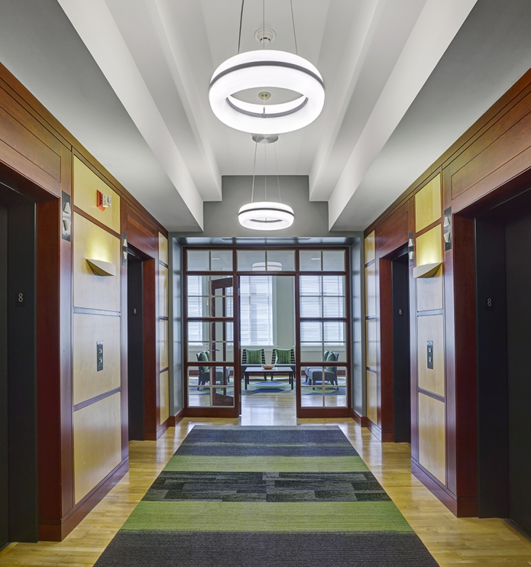 Meridian Round pendant is perfect for office lighting, seen here above a corridor in a modern design office.