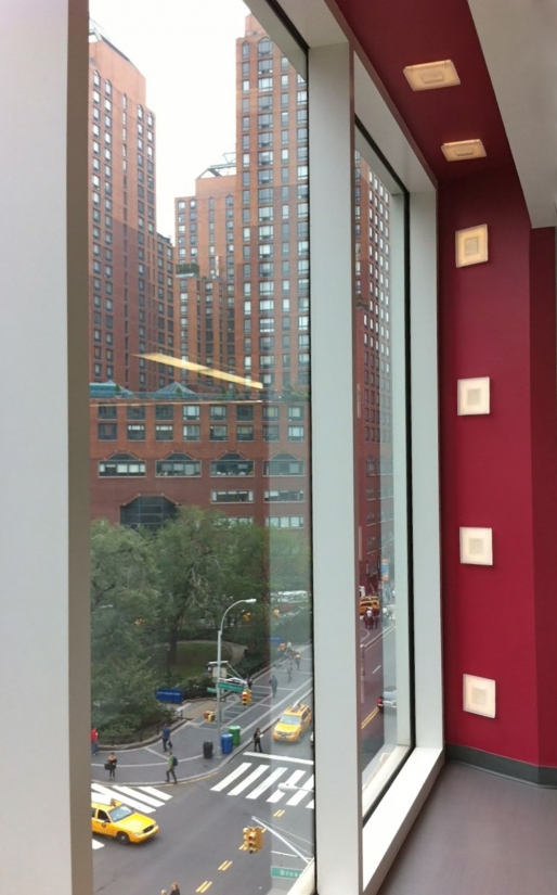 Merlin sconces as retail lighting fixtures around a large window overlooking the city street.