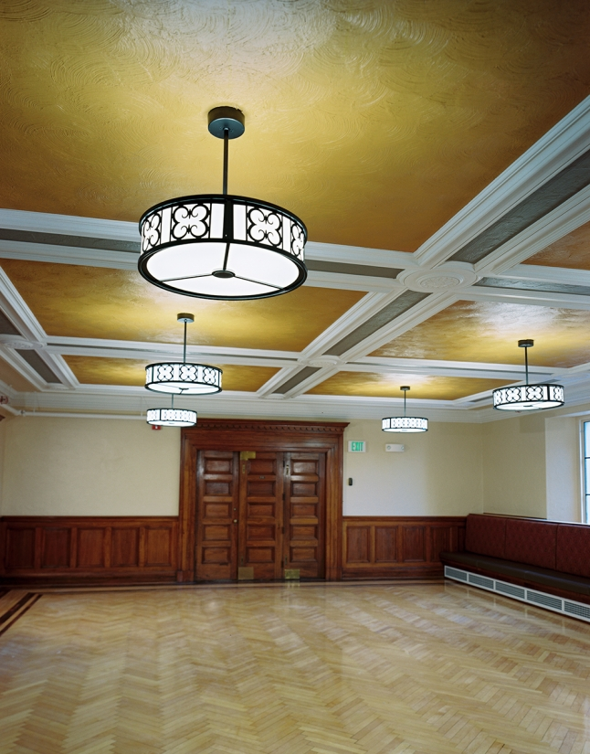 Midland Arts custom light fixtures hung from a classically designed, detailed ceiling, overlooking a polished wood floor.