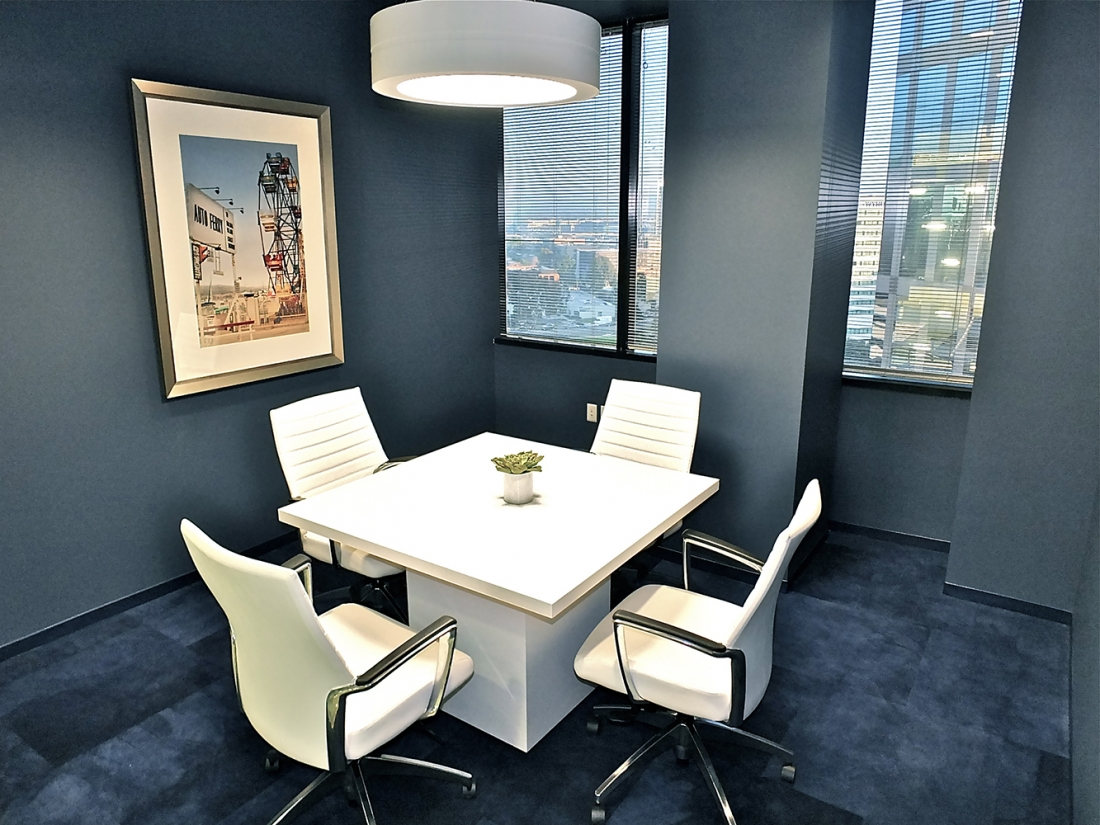 An Omnience pendant in an office lighting application above a small meeting table in a blue-carpeted meeting room.