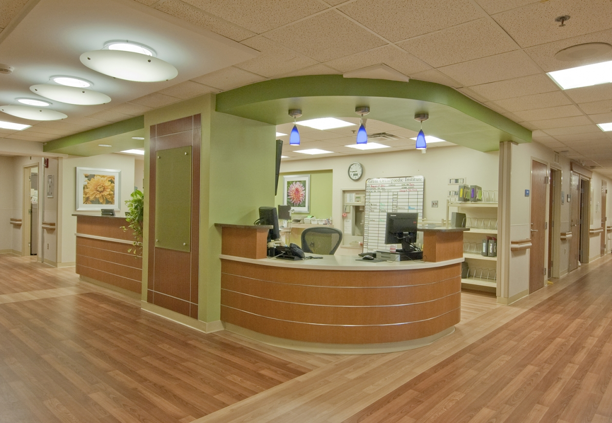 Ovation ceiling-mounted luminaires as hospital lighting along a warm-toned corridor.