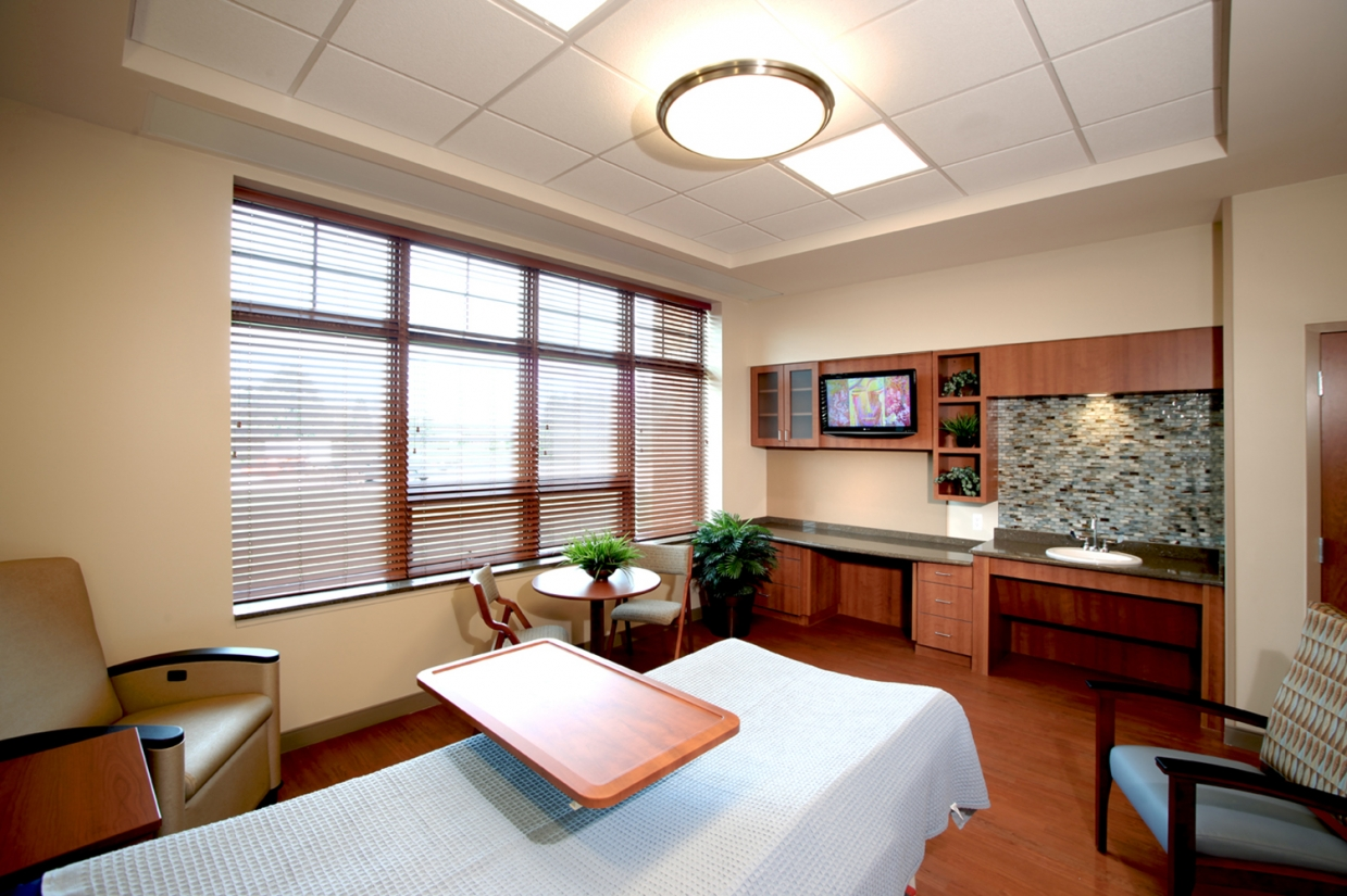 Ovation pendant in a patient room lighting application above a bed and seating area.