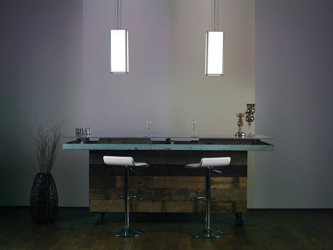 Parallel pendants as restaurant lighting above a modern bar seating area.