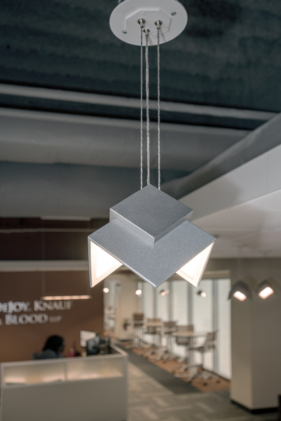 Petal OLED pendants are eye-catching office lighting fixtures, seen here above a workplace reception area.