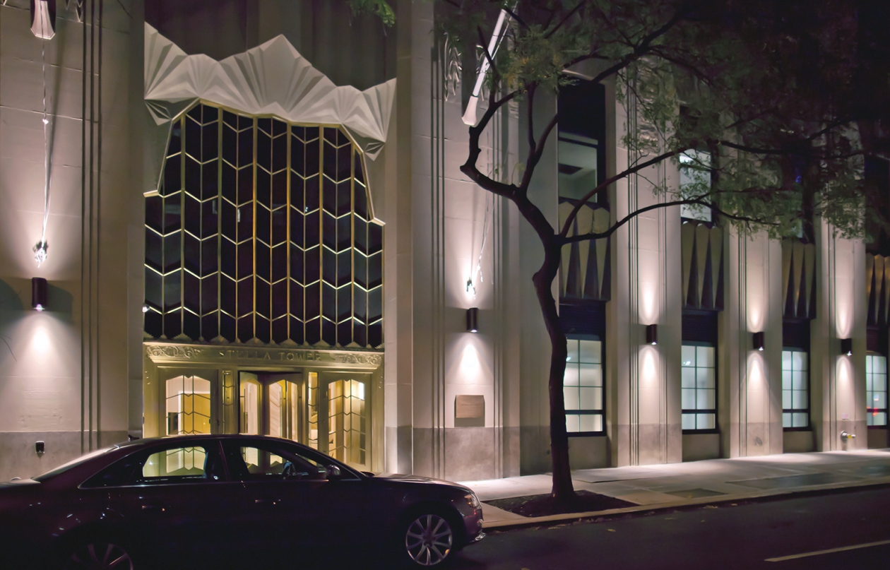 Pla exterior lighting fixtures provide uplight and downlight on a commercial building exterior at night.