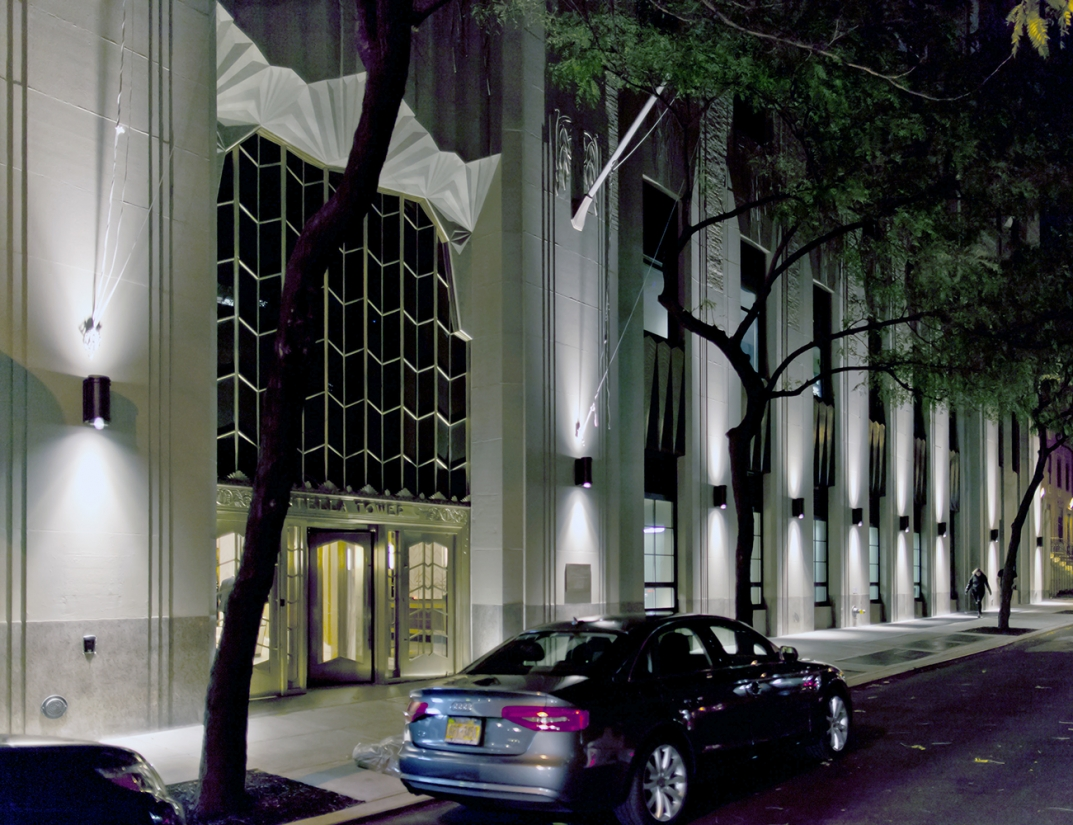 Pla outdoor light fixtures provide uplight and downlight on a commercial building exterior at night.