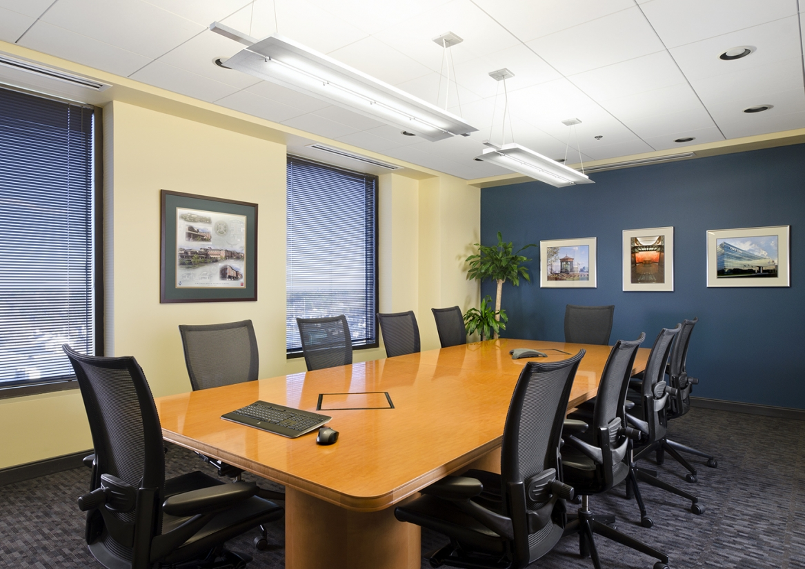Plana office lighting fixtures providing clean indirect light above a bright conference room table.