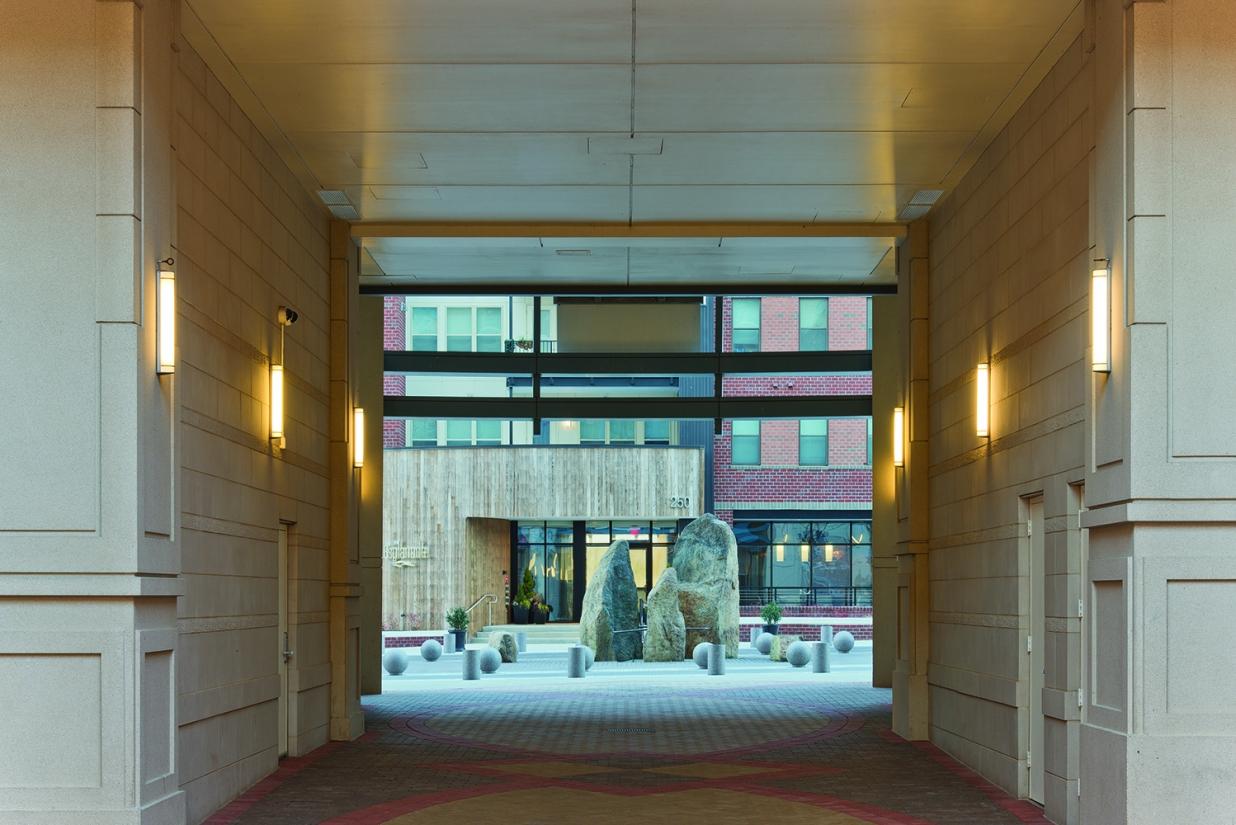Raven outdoor light fixtures along an exterior passageway between buildings in an outdoor commercial area.