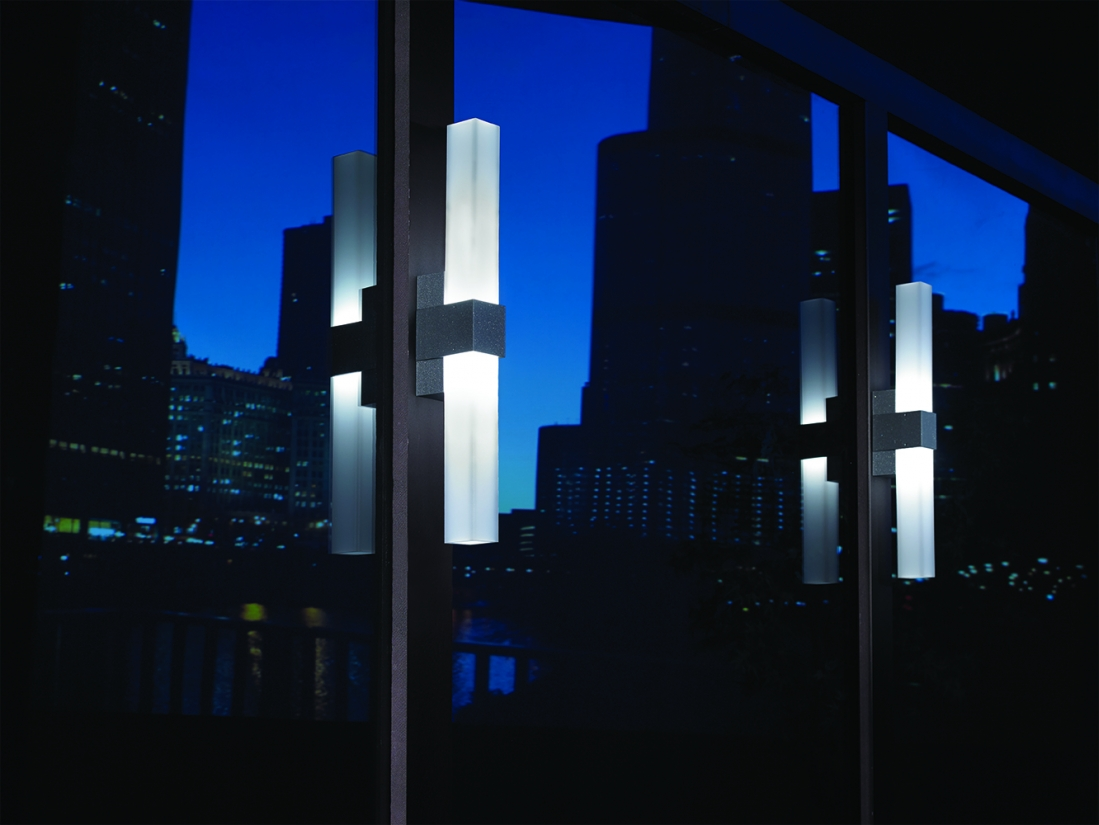 SASS exterior lighting fixtures between large windows at night, reflecting city buildings.