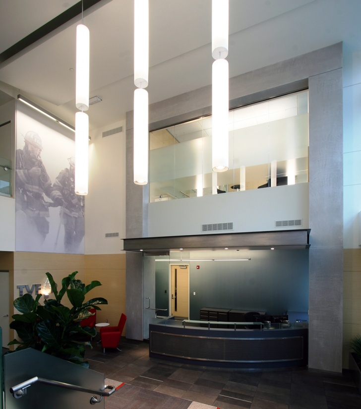 Sequence architectural lighting fixtures illuminate a fire department lobby and reception area.