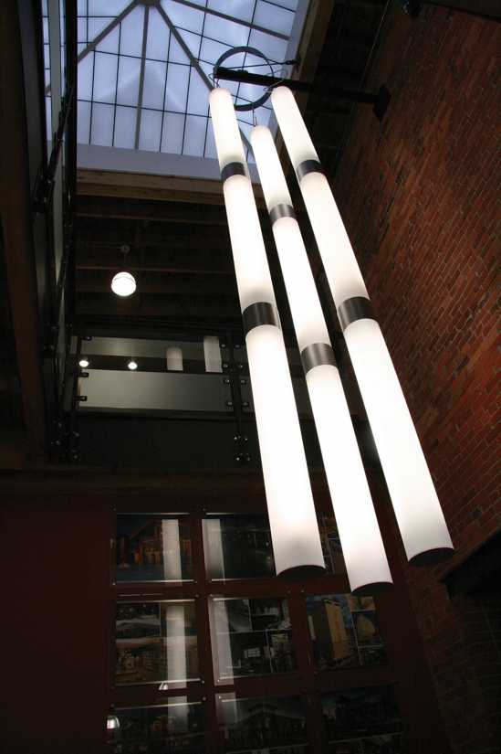 Sequence pendants linked in three tandem strands of three in a configuration of custom light-fixtures for an office lobby.