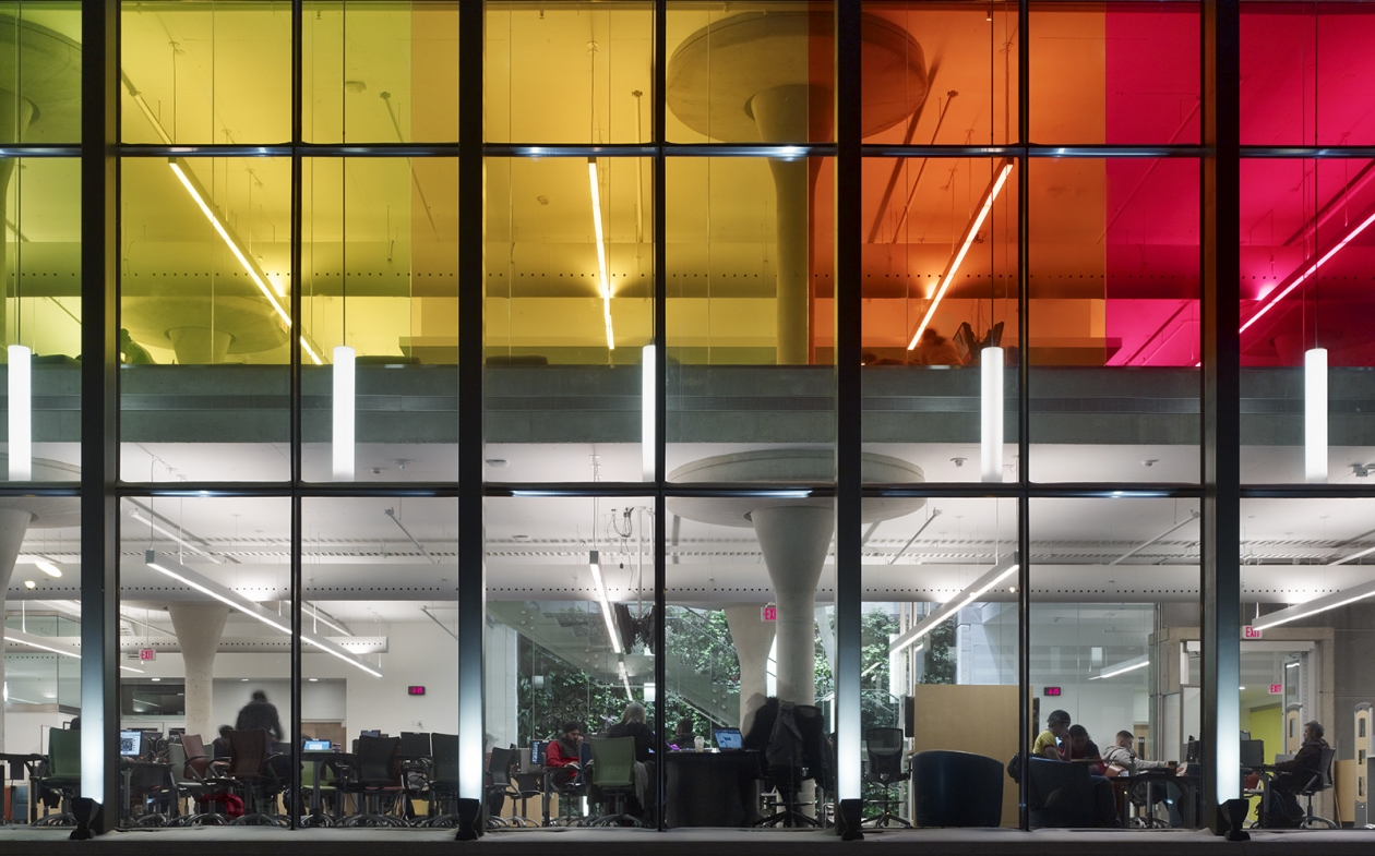 Sequence pendants for education lighting design visible from the exterior of a colorful campus building.