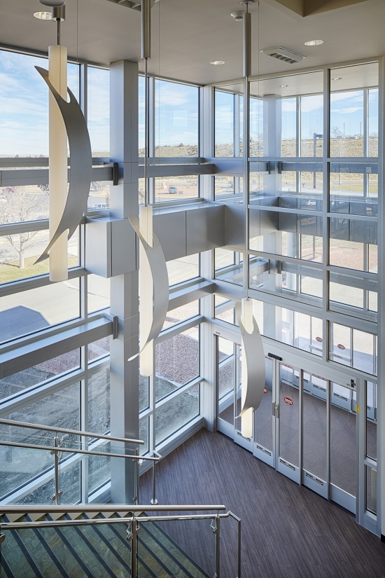 Sequence pendants enhance educational interior design in a well-lit exposed staircase.