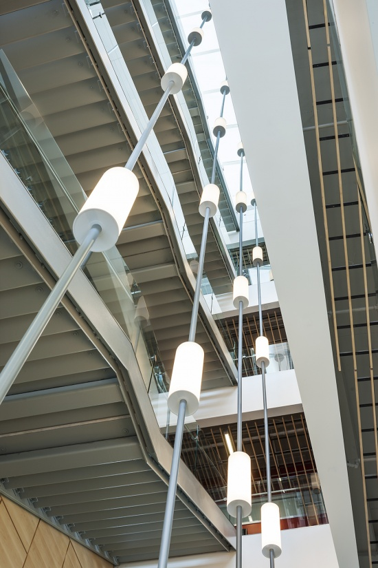 Sequence pendants enhance educational interior design in a tandem-mount configuration for a multi-level atrium.