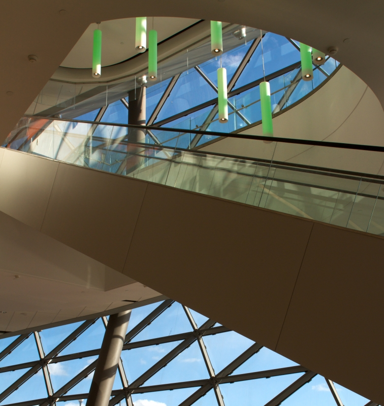Sequence modern lighting fixtures emit green light over an escalator in a large, well-lit convention center.