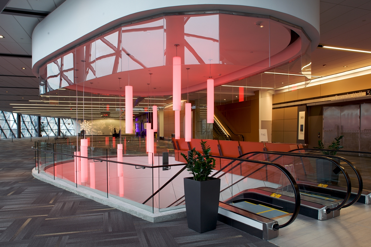Sequence modern lighting fixtures emit pink light above an escalator in a large, modern convention center.