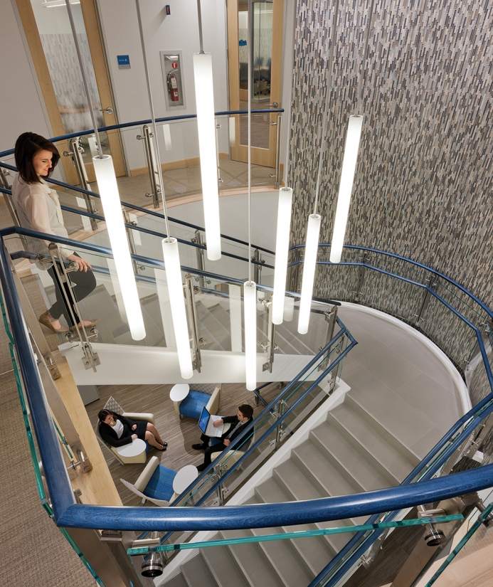 Sequence office lighting fixtures illuminate a modern staircase in a sleek multi-level office building.
