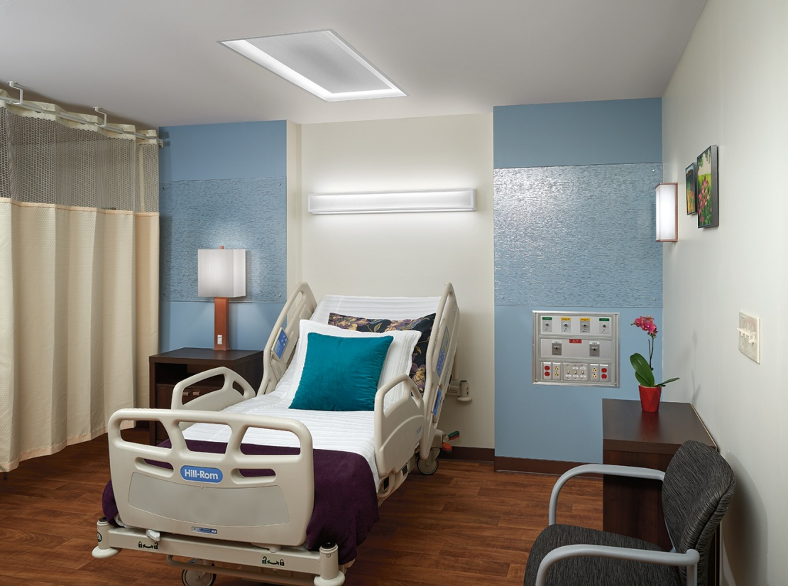 Serenity emits comforting overbed light and a matching table lamp for modern patient room lighting design.