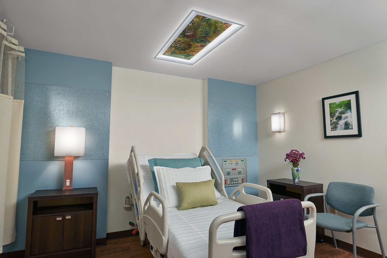 Serenity patient room lighting fixtures illuminate a hospital bed from a table lamp, Vara Kamin overbed luminaire, and wall sconce.