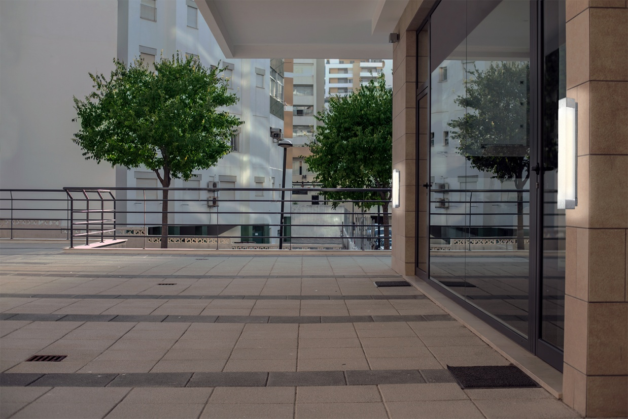 Shine outdoor light fixtures illuminate either side of a large glass door on a metropolitan terrace.