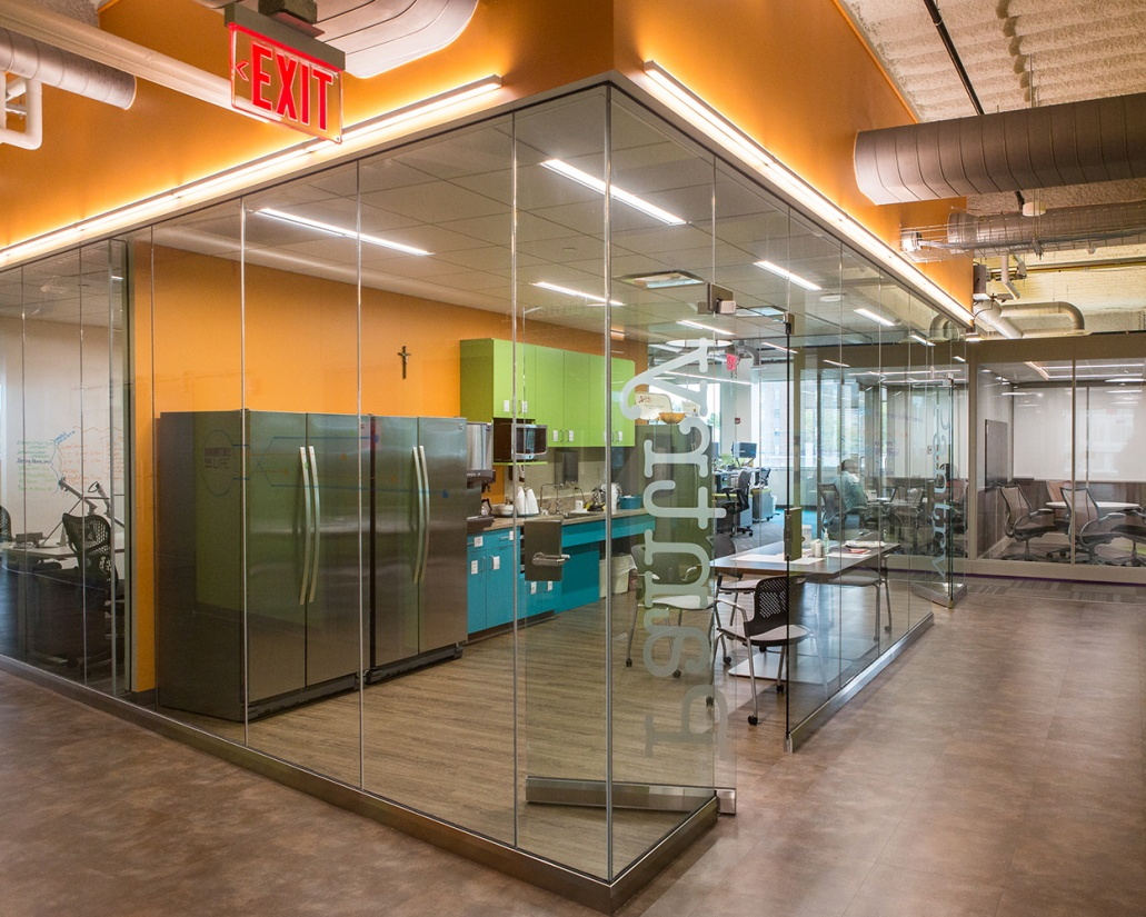 Sleight office lighting fixtures illuminate the edges of a glass-walled workplace kitchen.