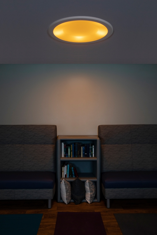 Symmetry behavioral health ceiling luminaire in nightlight mode over a yoga room