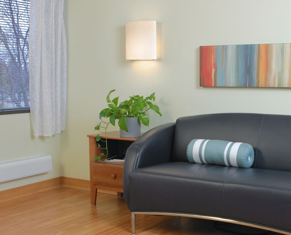 Unity wall sconce provides warm, inviting light in a hospitality lighting design near a sofa and side table.