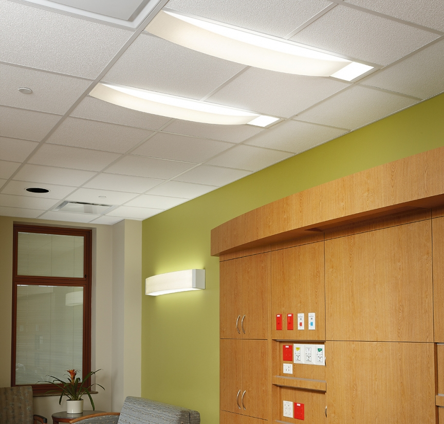 Unity medical lighting provides ceiling and wall lighting with pleasing, comforting shapes above a patient room seating area.
