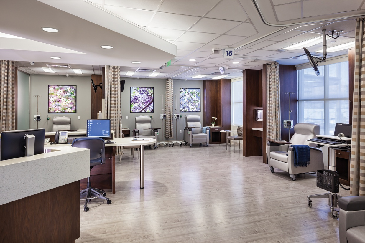 Unity medical lighting illuminates an infusion center with multiple patient seats and a nurse's station.