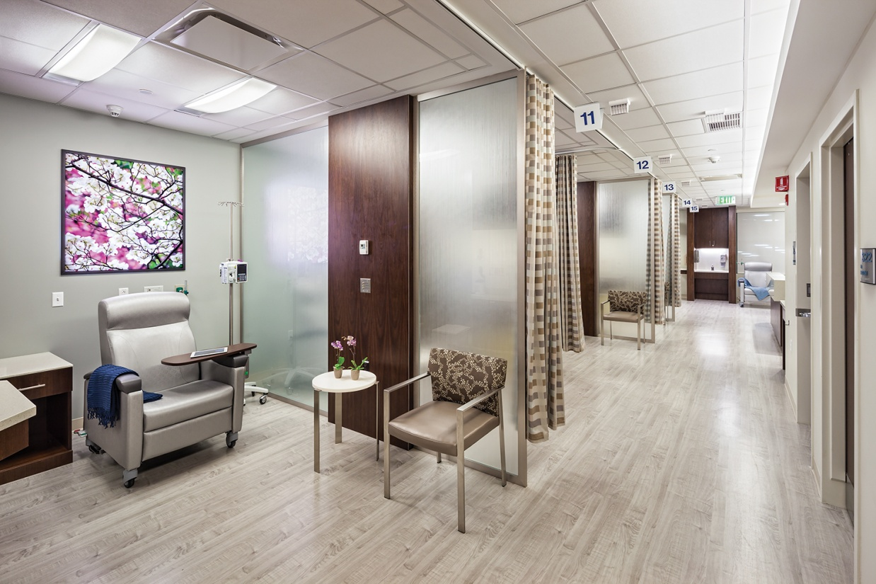 Unity patient room lighting illuminates an infusion station in an open treatment corridor.