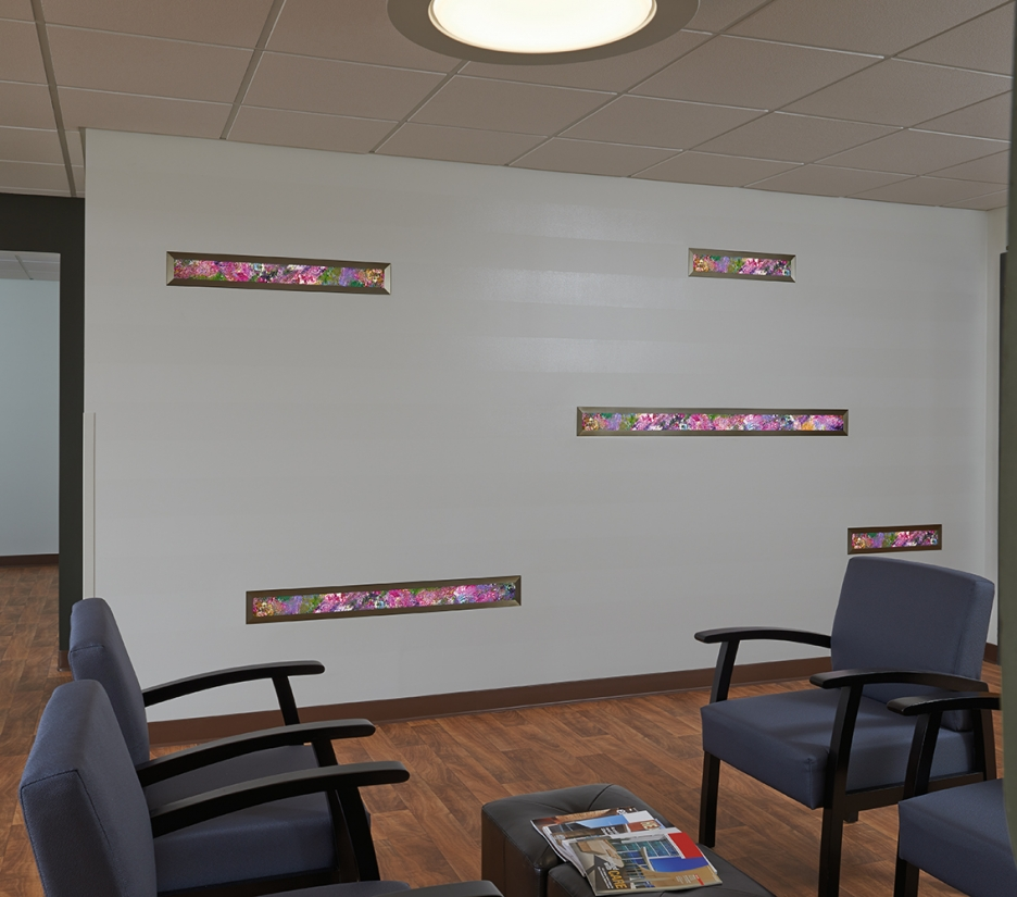 Visage medical lighting, featuring Vara Kamin artwork, illuminates the bed in a small exam room.