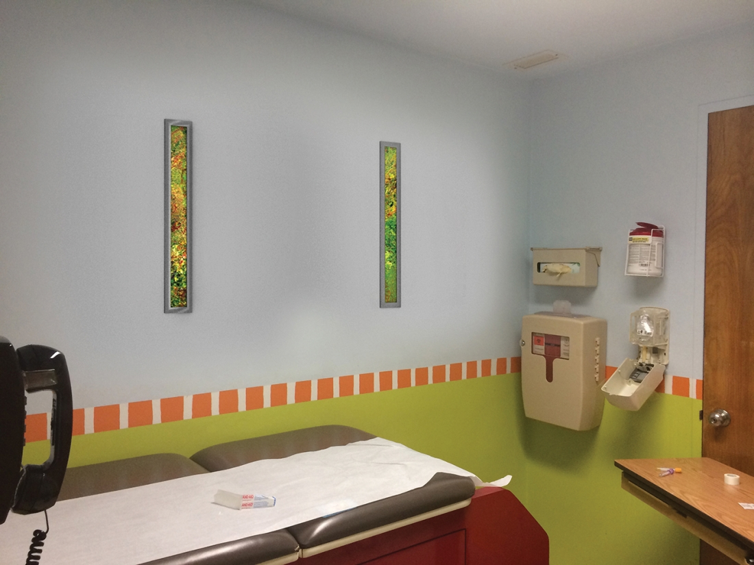 Visage medical lighting, featuring Vara Kamin artwork, illuminates the wall in a small waiting area.