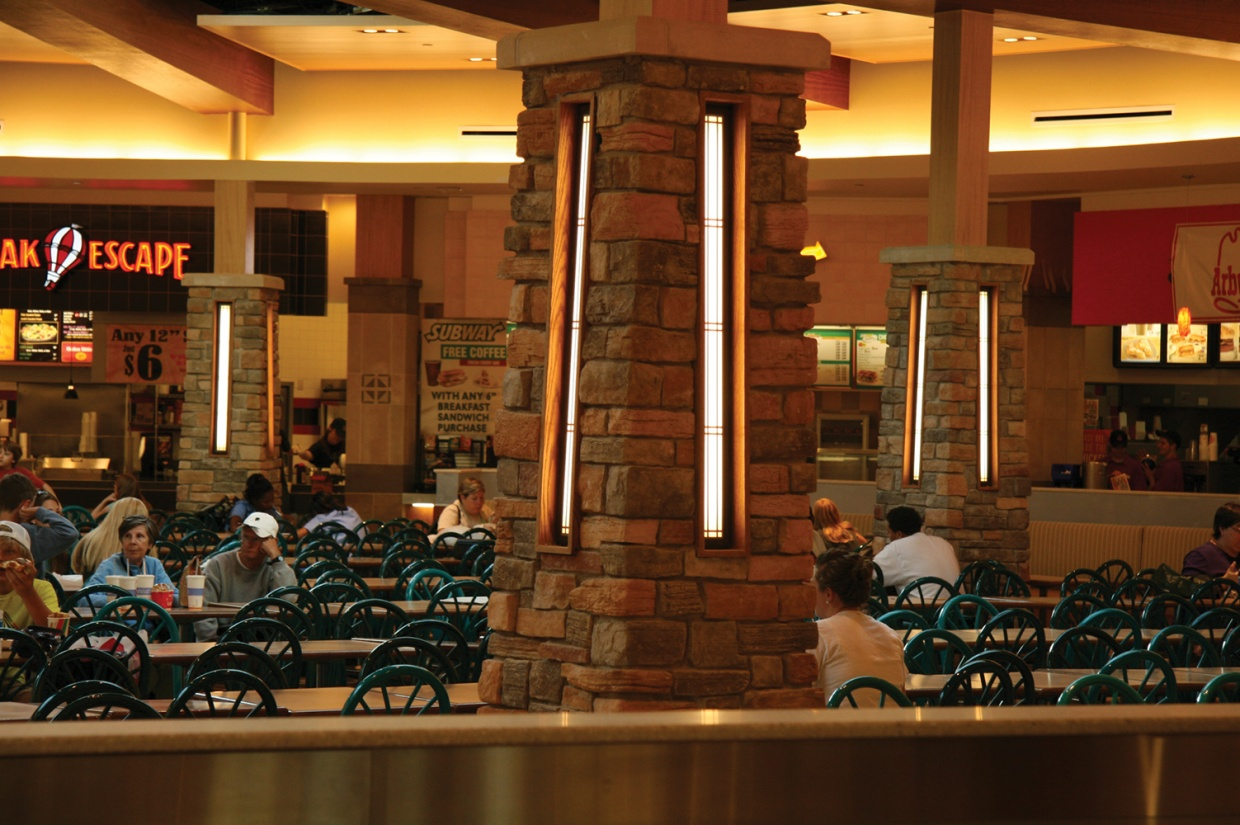 Visage sconces in a stone column provide eye-catching, modern lighting design in a busy mall food court.