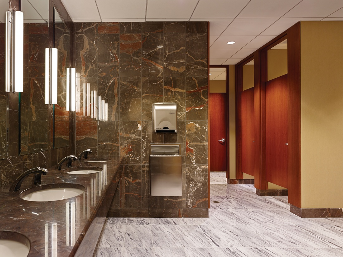 Voila modern vanity light fixtures illuminate mirrors in a public restroom with marble walls and countertops.