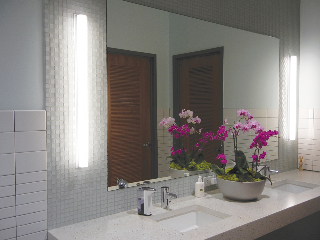 Voila modern vanity light fixtures illuminate mirrors in sleek, clean restroom with a bowl of purple flowers between two sinks.