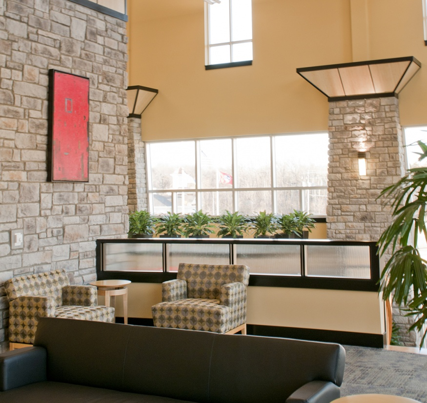 Wedge custom sconces illuminate commercial and office lighting designs, seen here on a stone wall in a seating area.