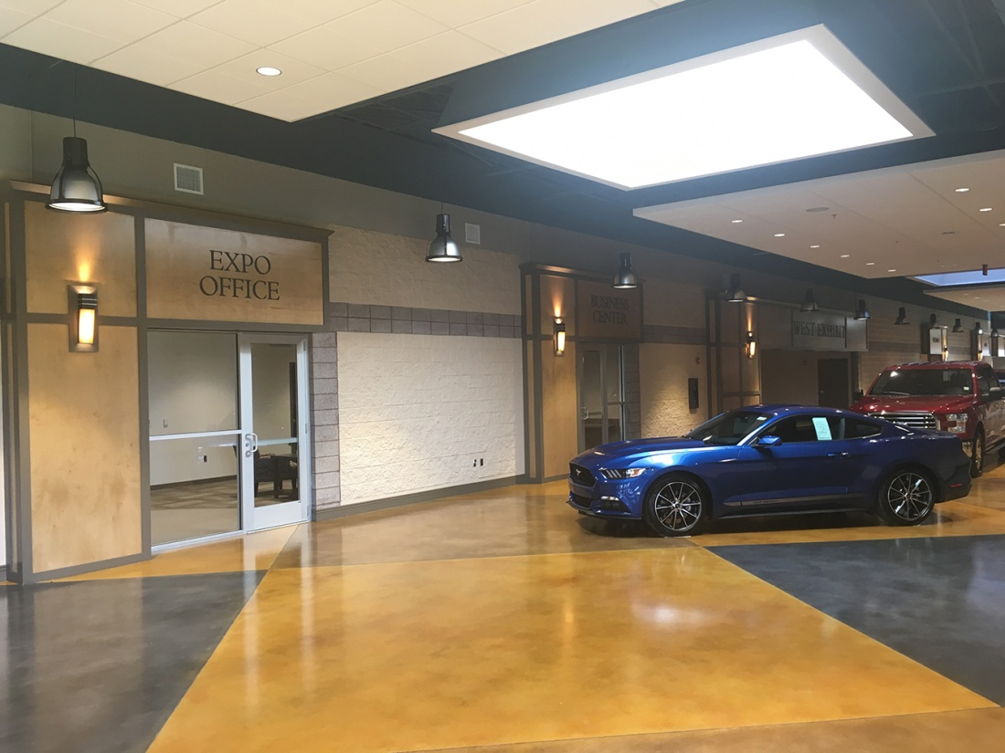 Wedge custom sconces for hospitality lighting designs illuminate an indoor expo center with new cars on display.