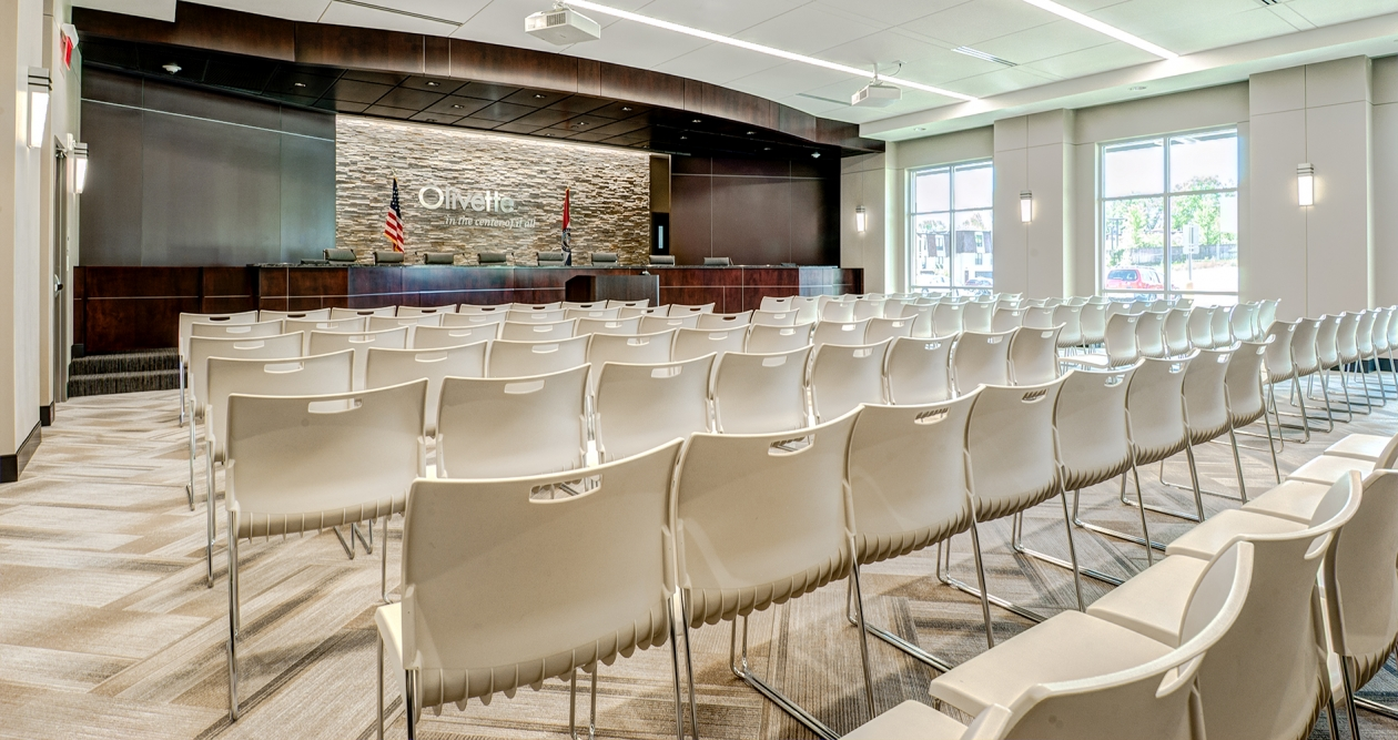 Wedge sconces provide sophisticated architectural lighting for a modern town meeting hall