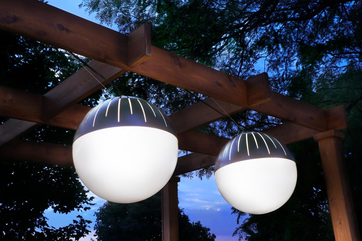 Zume outdoor light fixtures illuminate a wooden pergola structure below a darkening night sky and tall trees.