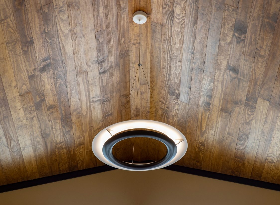Cosmo ring pendant suspended below a natural wood cathedral ceiling