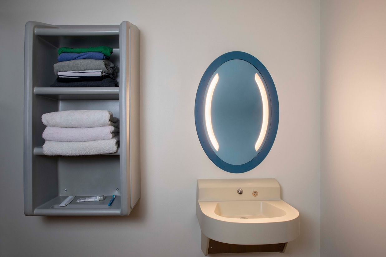 Sole oval illuminated mirror in a behavioral health bathroom