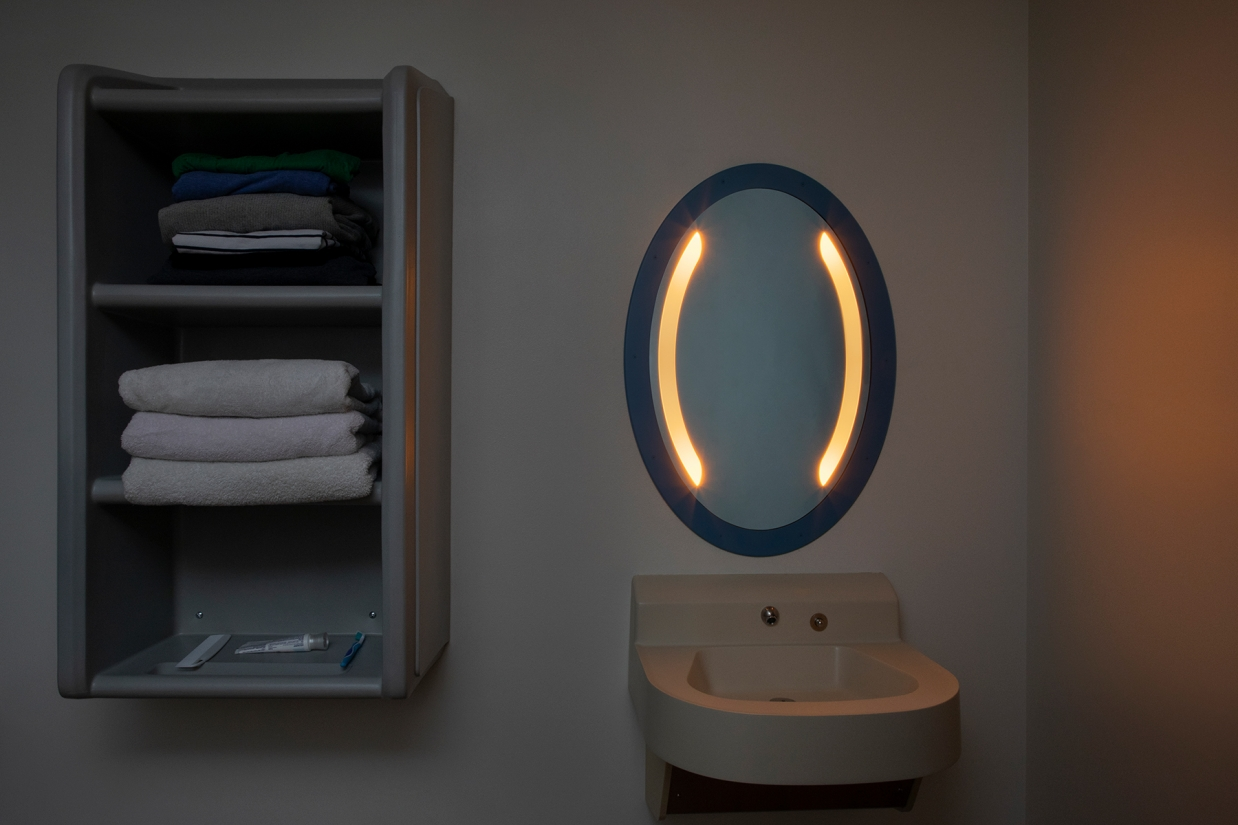Sole oval illuminated mirror in a behavioral health bathroom with nightlight mode on