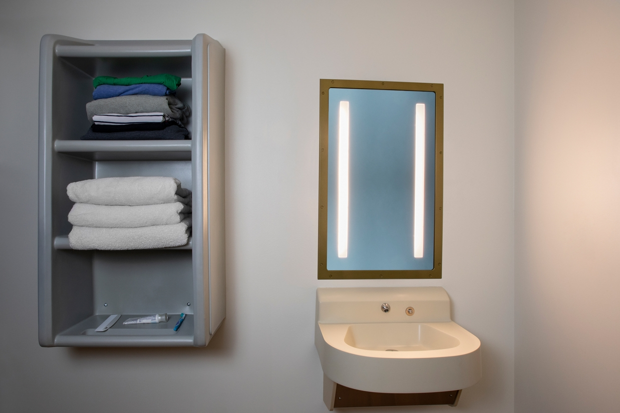 Sole rectangular illuminated mirror in a behavioral health bathroom