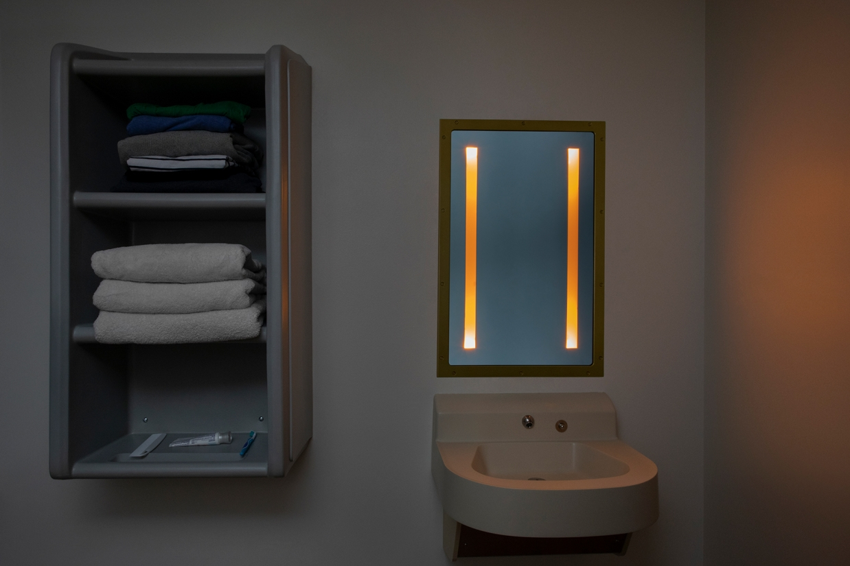 Sole rectangular illuminated mirror in a behavioral health bathroom with nightlight mode on
