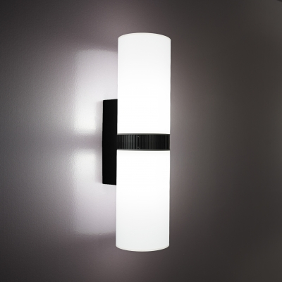 A luminous cylinder wall sconce with a dark finish bar in the center