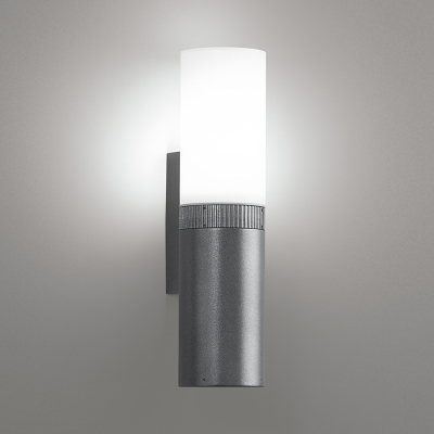 An outdoor wall sconce with a cylinder body that's solid on the bottom and luminous on the top