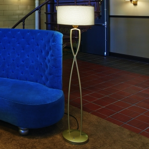 A curvy floor lamp with a round shade next to a blue sofa