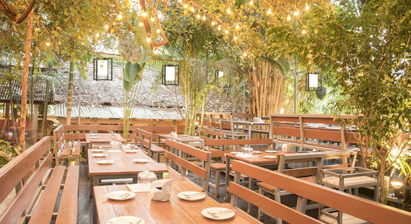 Lanterna outdoor pendant lighting fixture over a patio seating area at restaurant